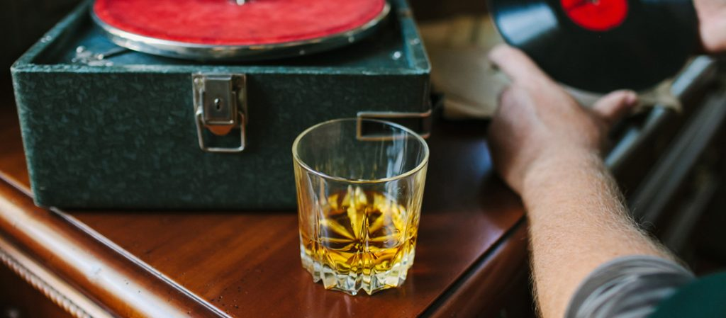 Vintage vinyl record, vintage gramophone and glass of whiskey